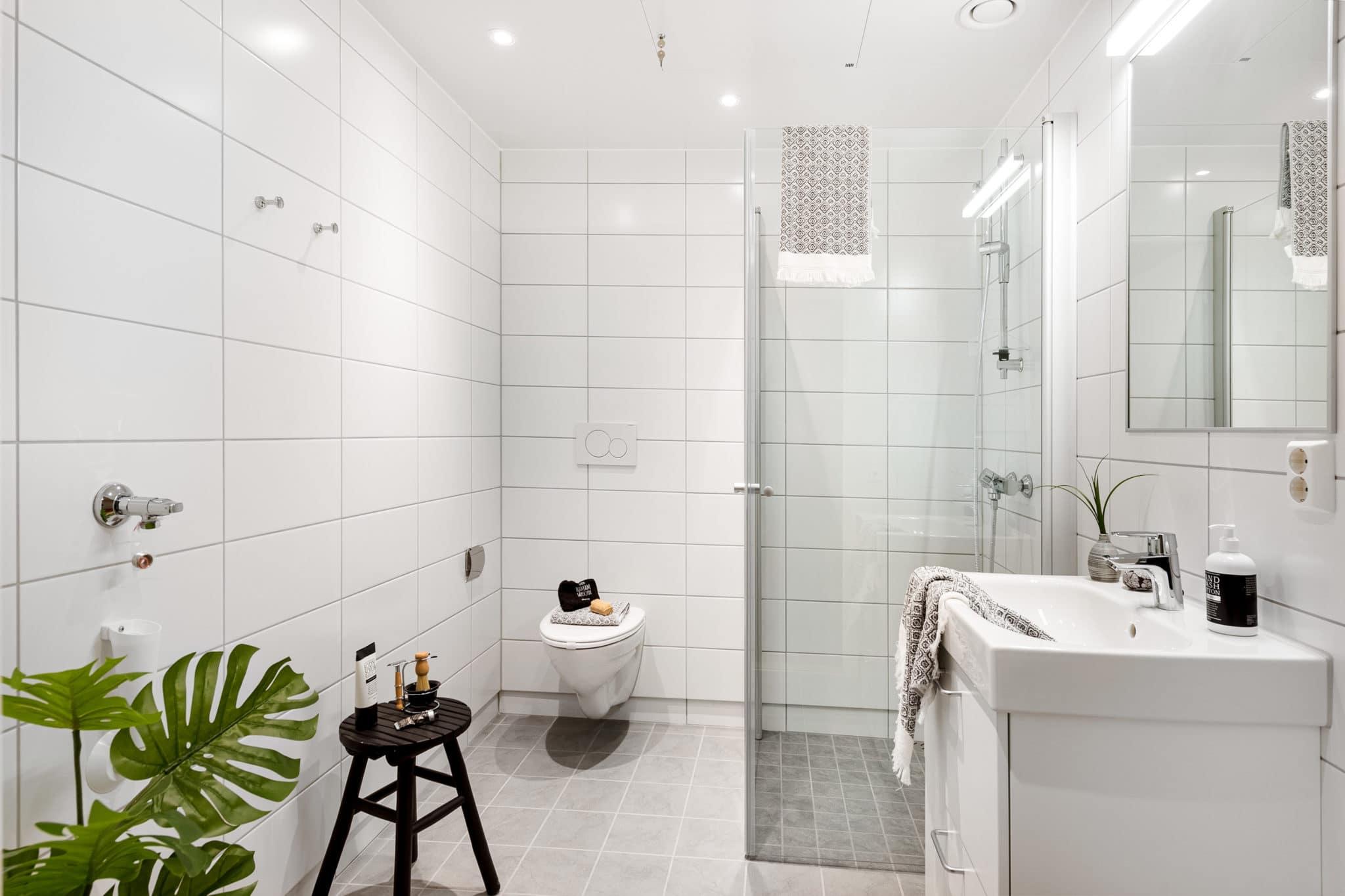 HVitt baderom med fliser toalett og vask