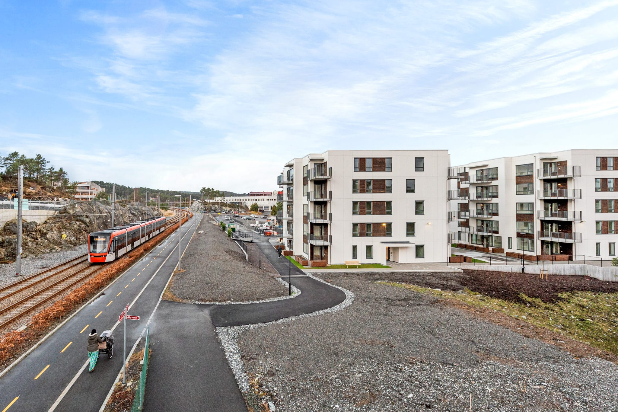 Hvite bygninger med vei og bybane tog foran