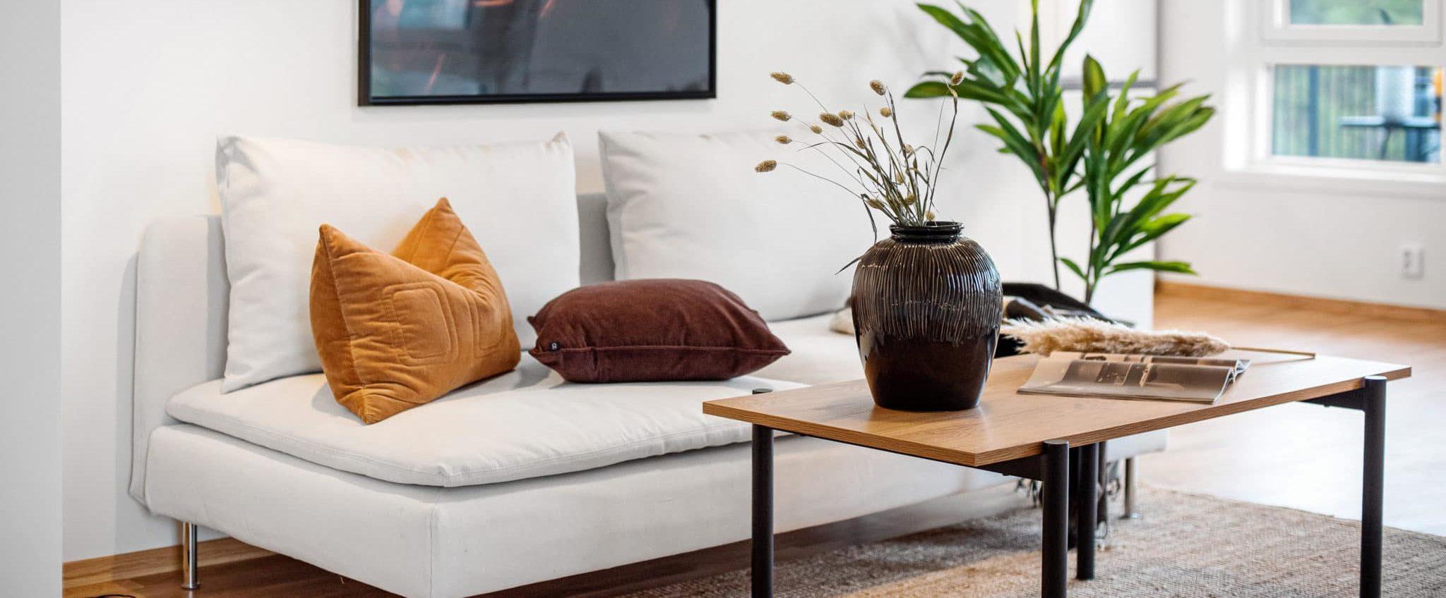 sofa med puter og bord med blomster